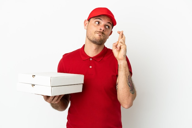 Доставщик пиццы в рабочей форме собирает коробки для пиццы над изолированной белой стеной, скрещивая пальцы и желая всего наилучшего