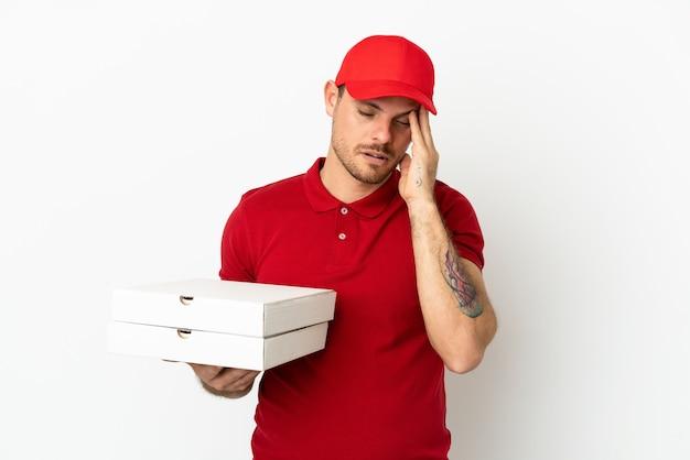 Доставщик пиццы в рабочей униформе собирает коробки для пиццы на изолированной белой стене с головной болью