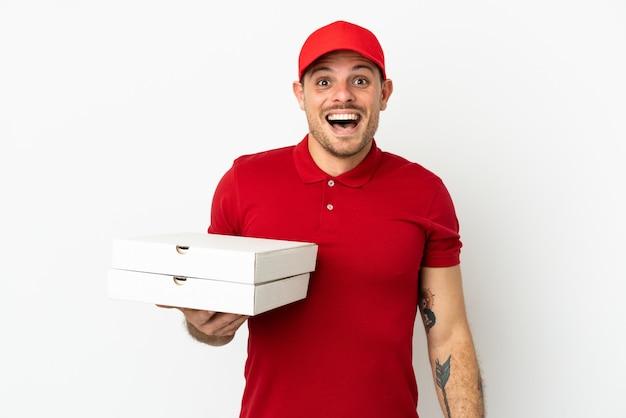 Доставщик пиццы в рабочей униформе собирает коробки из-под пиццы над изолированной белой стеной с удивленным выражением лица
