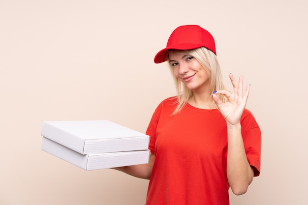 Pizza delivery russian woman holding a pizza over isolated wall showing ok sign with fingers