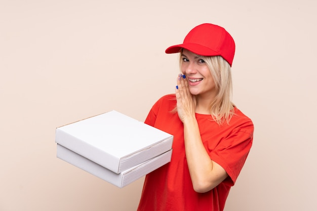 Pizza delivery russian woman holding a pizza over isolated wall whispering something