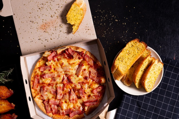 Pizza delivery service in a cardboard box with cheese garlic bread and new orleans wings