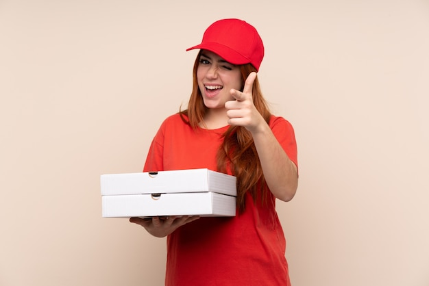 Pizza delivery teenager girl holding a pizza points finger at you