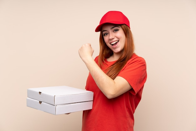Pizza delivery teenager woman holding a pizza celebrating a victory