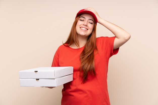 Pizza delivery teenager woman holding a pizza laughing