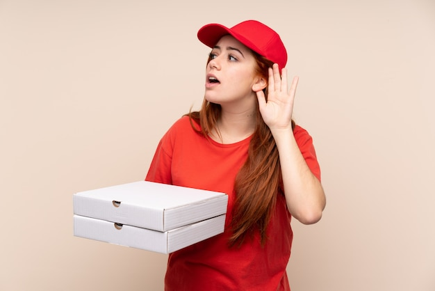 Pizza delivery teenager woman holding a pizza listening something