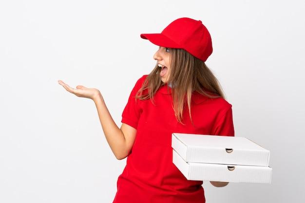 Женщина-доставщик пиццы держит пиццу и защищает от коронавируса с помощью маски над изолированной белой стеной с удивленным выражением лица