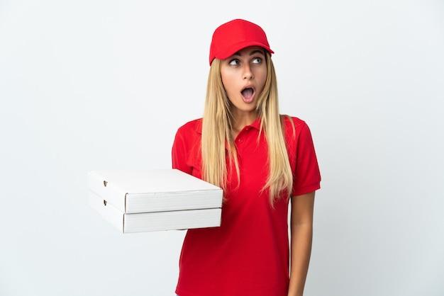 見上げると驚きの表情で白い背景で隔離のピザを保持しているピザ配達の女性