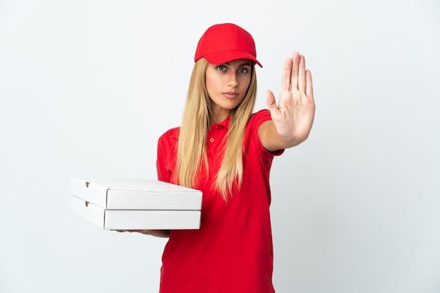 Женщина доставки пиццы, держащая пиццу, изолированные на белом фоне, делая жест остановки