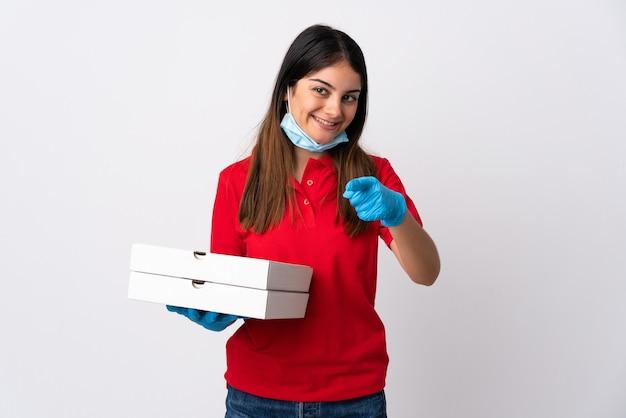 白い背景で隔離のピザを保持しているピザ配達女性は自信を持ってあなたに指を指