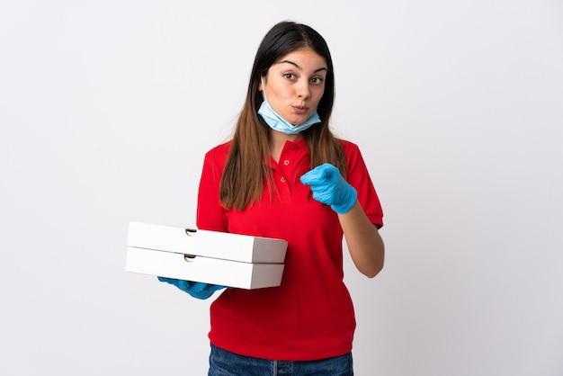白い背景で隔離のピザを保持しているピザ配達の女性は驚いて正面を指しています