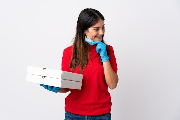 アイデアを考えて側面を見て白い背景で隔離のピザを保持しているピザ配達の女性