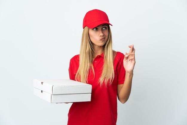 指が交差し、最高を願って白い背景で隔離のピザを保持しているピザ配達の女性