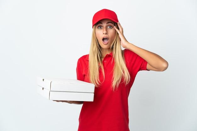 驚きの表情で白い背景で隔離のピザを保持しているピザ配達女性