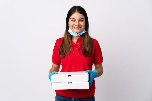 たくさん笑って白で隔離のピザを保持しているピザ配達の女性
