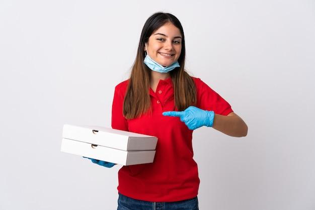白い壁に隔離されたピザを保持し、それを指すピザ配達の女性
