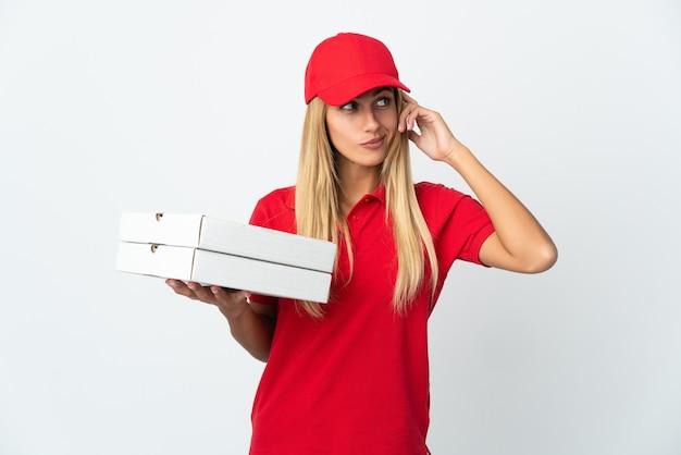 疑問と考えを持って白い壁に隔離されたピザを保持しているピザ配達の女性