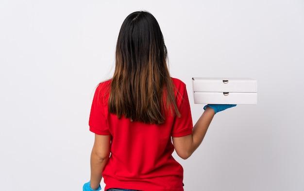 後ろの位置で白い壁に分離されたピザを保持しているピザ配達の女性