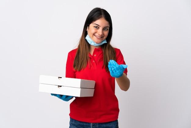 白い壁に隔離されたピザを手に持って来るように誘うピザ配達の女性。あなたが来て幸せ