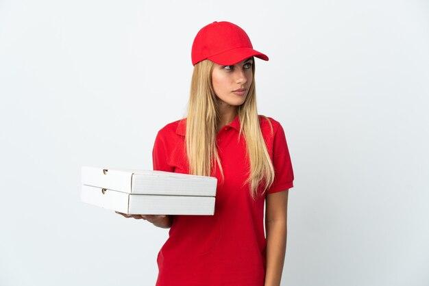Женщина-доставщик пиццы, держащая пиццу, изолированную на белой стене, глядя в сторону