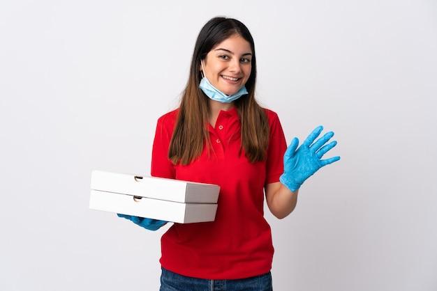 행복 한 표정으로 손으로 경례 흰 벽에 고립 된 피자를 들고 피자 배달 여자