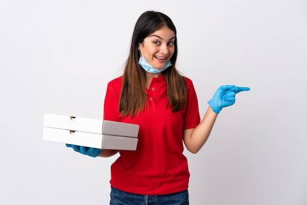 흰 벽에 고립 된 피자를 들고 피자 배달 여자 놀라게하고 측면에 손가락을 가리키는