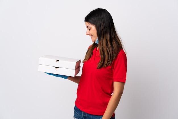幸せな表情で白で隔離のピザを保持しているピザ配達の女性