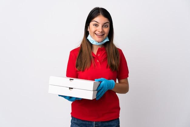 Женщина-доставщик пиццы, держащая пиццу, изолированную на белом, с удивленным и шокированным выражением лица