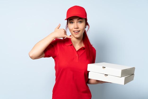 電話ジェスチャーを作る孤立した壁にピザを置くピザ配達の女性。コールバックサイン