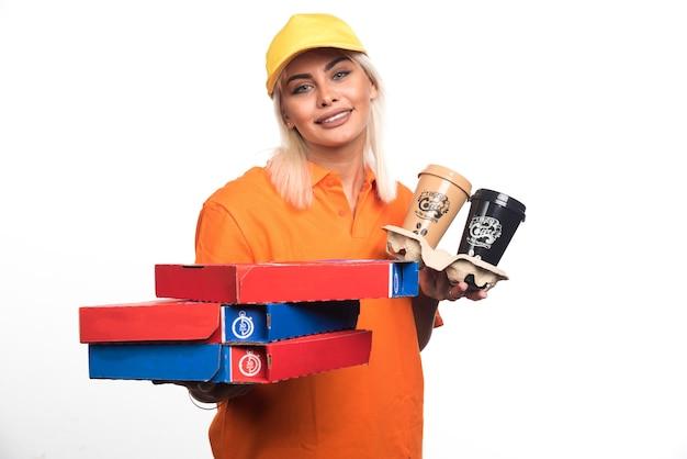 Женщина доставки пиццы, держащая пиццу и кофе на белом фоне. фото высокого качества