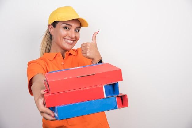 Женщина доставки пиццы держа коробки пиццы делая большие пальцы руки вверх на белой предпосылке.