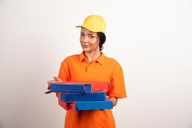 Donna di consegna della pizza che tiene i contenitori per pizza sulla parete bianca.