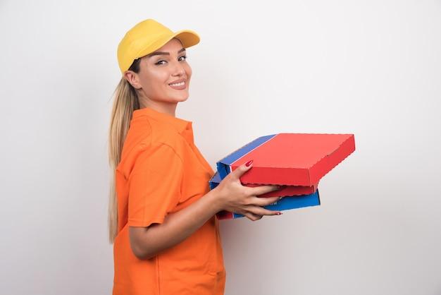 白いスペースに平和な顔でピザの箱を保持しているピザ配達の女性