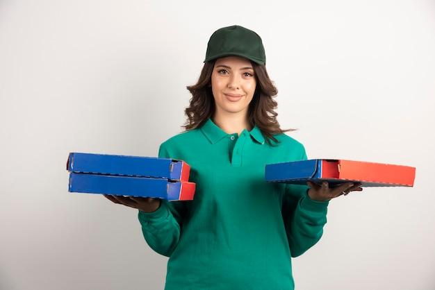 Donna di consegna della pizza che tiene le scatole della pizza.