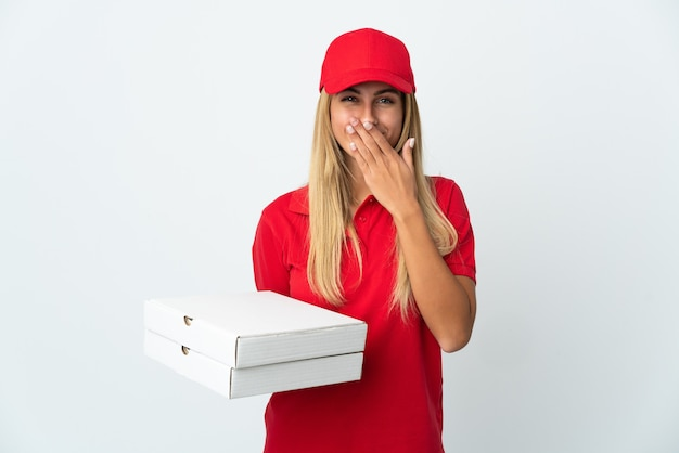 Pizza delivery woman holding a pizza isolated on white wall happy and smiling covering mouth with hand