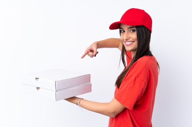 Pizza delivery woman holding a pizza over isolated white wall and pointing it