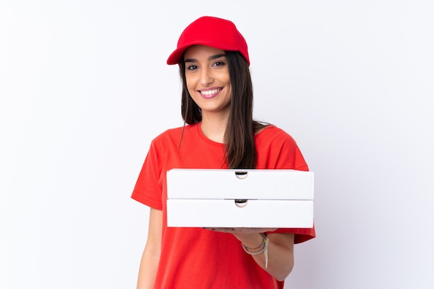 Pizza delivery woman holding a pizza over isolated white wall smiling a lot