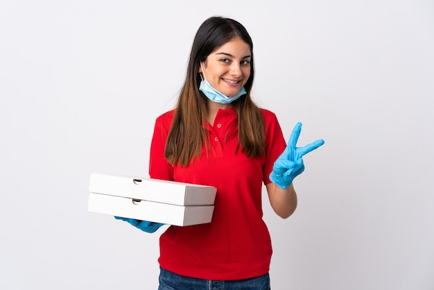 Pizza delivery woman holding a pizza isolated on white wall smiling and showing victory sign