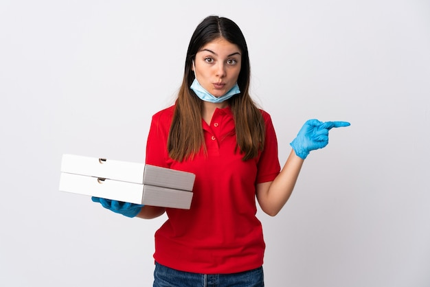 Pizza delivery woman holding a pizza isolated on white wall surprised and pointing side