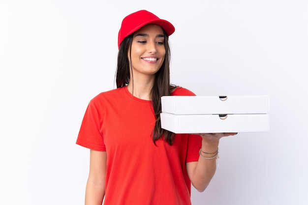 Pizza delivery woman holding a pizza over isolated white wall with happy expression