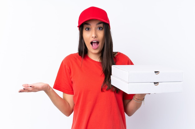Pizza delivery woman holding a pizza over isolated white wall with shocked facial expression