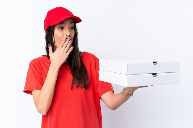 Pizza delivery woman holding a pizza over isolated white wall with surprise and shocked facial expression