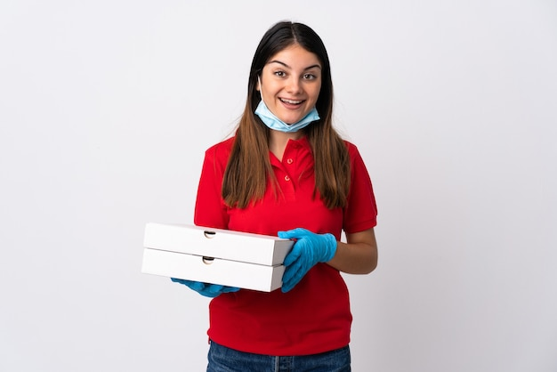 Pizza delivery woman holding a pizza isolated on white with surprise and shocked facial expression
