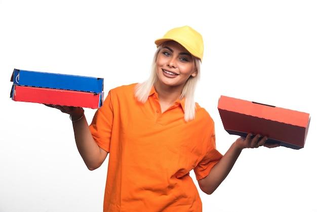 웃 고있는 동안 흰색 배경에 피자를 들고 피자 배달 여자. 고품질 사진