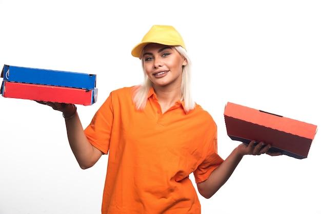 笑顔で白い背景にピザを保持しているピザ配達の女性。高品質の写真