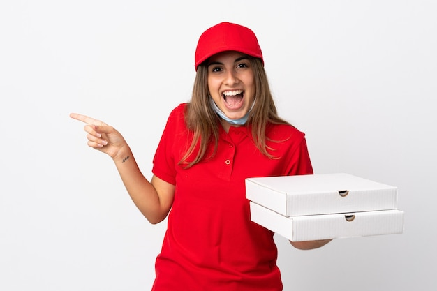 Pizza delivery woman holding a pizza and protecting from the coronavirus with a mask over isolated white wall surprised and pointing finger to the side