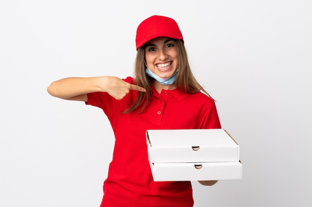 Pizza delivery woman holding a pizza and protecting from the coronavirus with a mask over isolated white wall with surprise facial expression