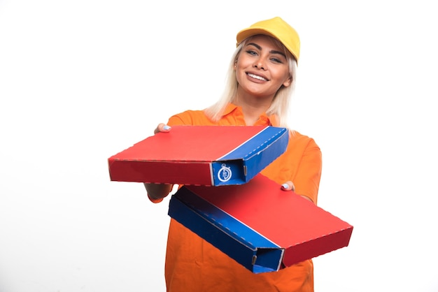 Pizza delivery woman holding pizza on white background while looking them. high quality photo