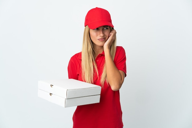 Pizza delivery woman holding a pizza on white frustrated and covering ears