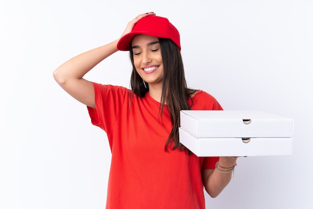 Pizza delivery woman holding a pizza over white wall has realized something and intending the solution